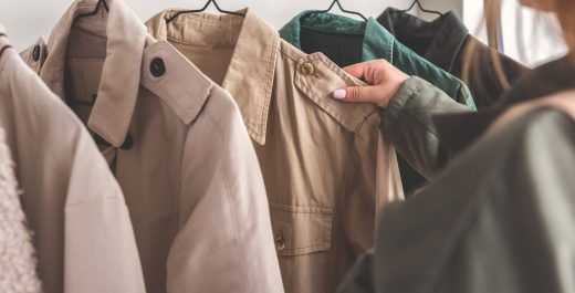 Girl is standing near hangers with overcoats and choosing one. Close up of female hand taking article of clothing. Copy space on left side